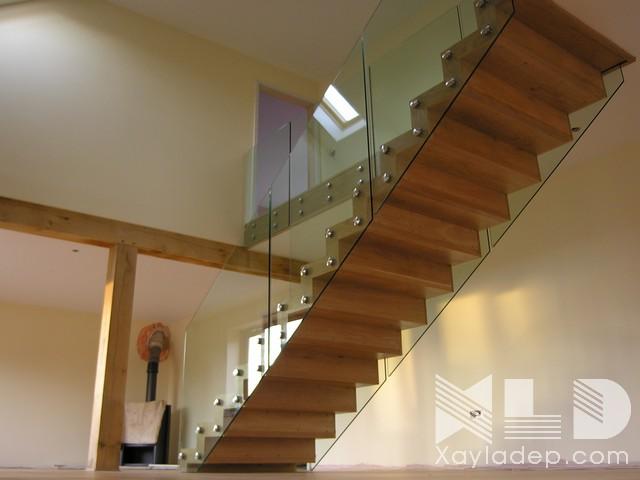 Đơn giản nhưng hiện đại, mẫu cầu thang này sử dụng hoàn toàn chất liệu gỗ tự nhiên kết hợp với nó là hệ thống kinh cường lực và các hệ thống vít.