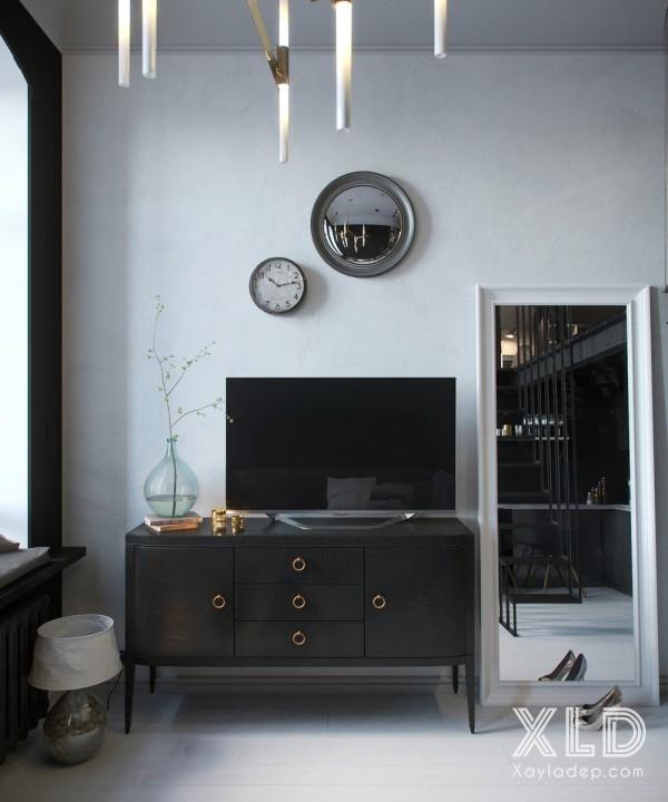 Các tay nắm mạ đồng trên các đồ gỗ nội thất màu đen đem 1 vẻ sang trọng và quý phải hơn cho căn hộ. Bên cạnh chiếc tủ tivi là chiếc gương Ample với khung viền kim loại vừa có tác dụng soi gương vừa mở rộng thêm diện tích của căn hộ