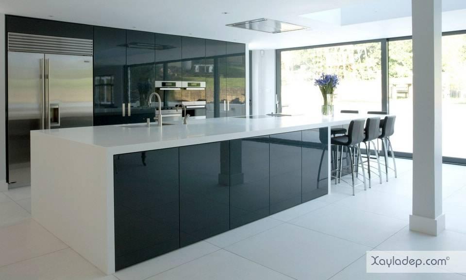 Tủ bếp acrylic màu xanh đen nhẹ nhàng nổi bật trong nhà bếp với ánh sáng rực rỡ. Hòn đảo bếp được hoàn thiện với chất liệu tương tự đem đến cái nhìn hài hòa