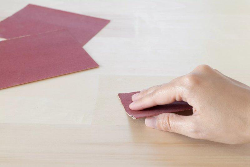 Giấy nhám đỏ chà bề mặt gỗ keo siêu dính bằng tay