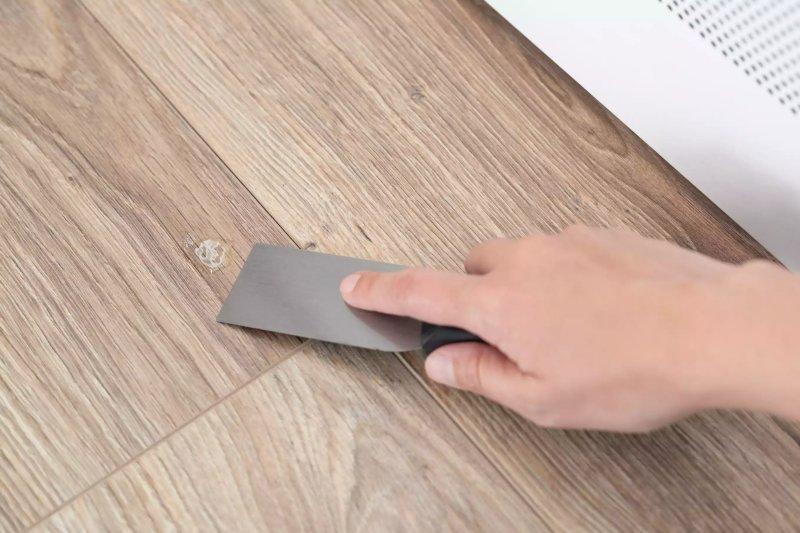 Dùng dao cạo sơn cạo keo siêu dính khỏi bề mặt gỗ