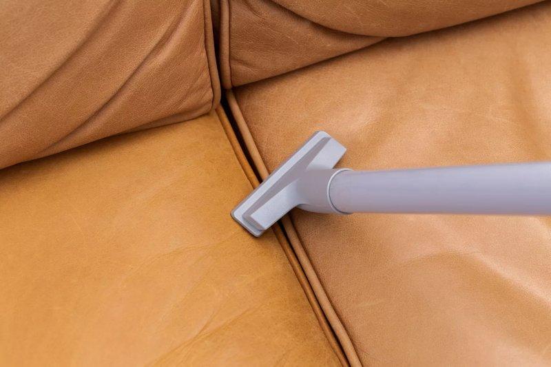 Hút bụi bằng vòi hút chuyên dụng giữa ghế sofa da
