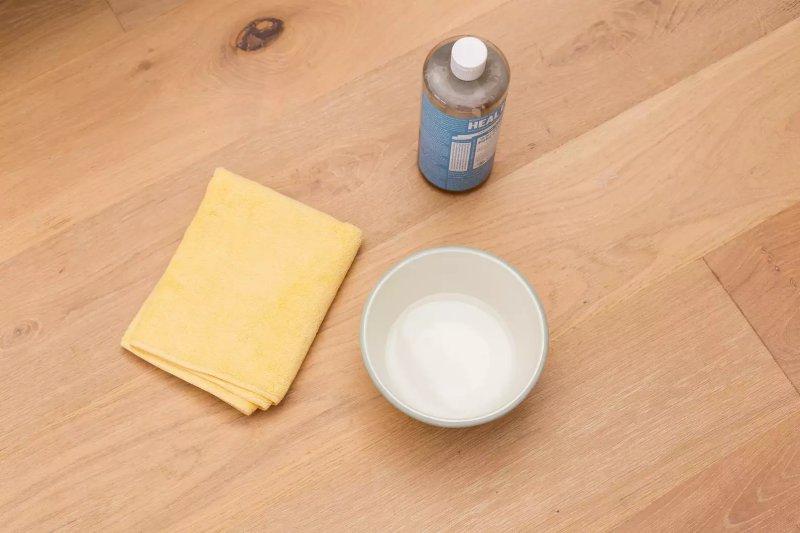 Chai xà phòng nhẹ bên cạnh vải sợi nhỏ và bát đựng dung dịch tẩy rửa chứa nước
