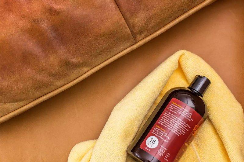 Chai dầu dưỡng da thương mại trên chiếc khăn sợi nhỏ màu vàng để khôi phục sự mềm mại của ghế sofa da
