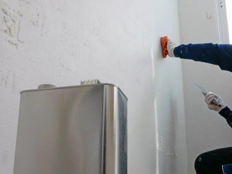 Hình ảnh một người thợ đang chuẩn bị bề mặt sơn tường với một hộp dung môi pha sơn chuẩn bị trước