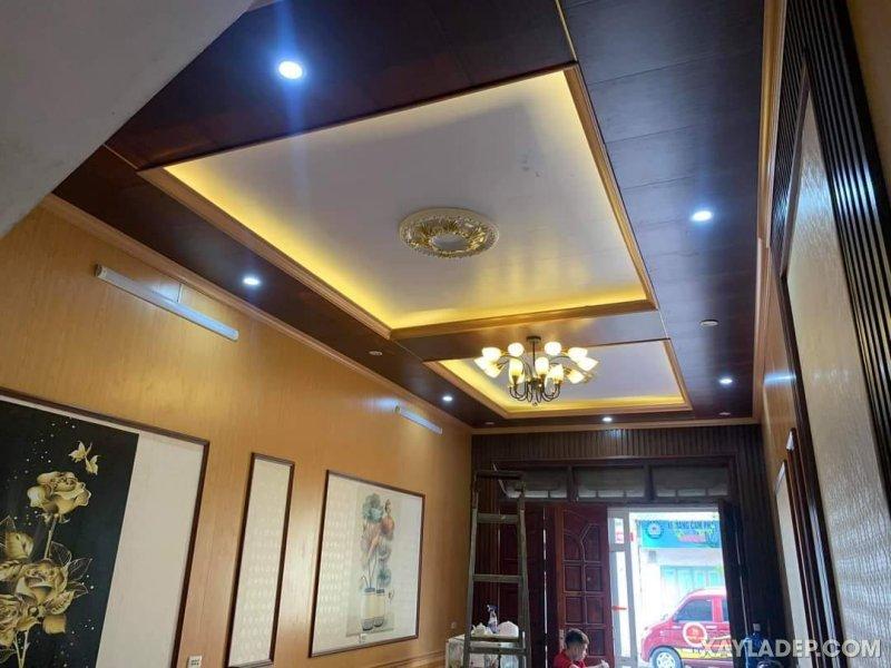 08   Một phòng khách nhà ống thi công trần nhựa giải gỗ kết hợp với ốp tường